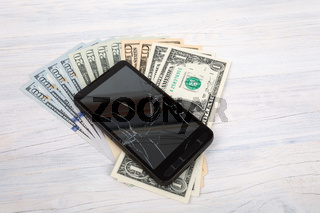 cracked cellular phone and American money on white