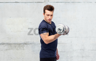sportive man flexing muscles with dumbbell
