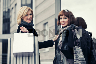 Two young fashion women with shopping bags next to mall door