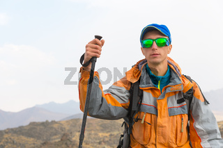 A guy with a wearing sunglasses in a membrane jacket, cap, with a backpack and sticks for Nordic walking, a traveler standing and looking at the mountains