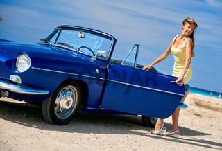 Beautiful woman near retro cabriolet car on the tropical beach. Idyllic scenery