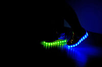 Fashionable sneakers with LED lighting on the legs of a girl with green and blue colors