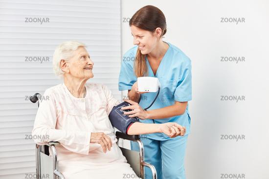 Pflegekraft misst den Blutdruck einer Seniorin