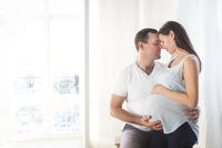 Pregnant woman and young man together indoors