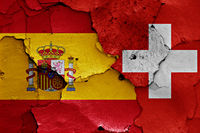 flags of Spain and Switzerland painted on cracked wall