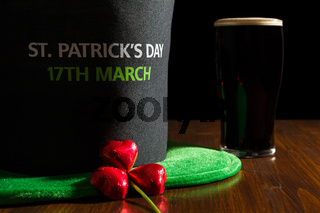 Closeup of St Patrick day with a pint of black beer, hat and shamrock over a table