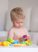 Boy playing with colorful modeling clay (plasticine or dough)