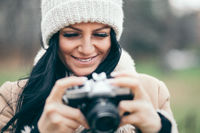 Female photographer taking pictures outdoors with an old vintage camera