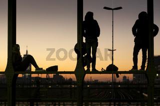 Menschen auf der Hackerbrücke in München bei Sonnenuntergang