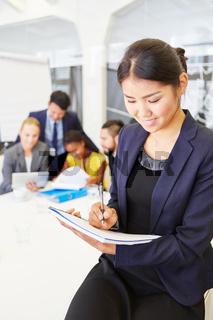 Asiatische Frau als Consultant macht sich Notizen