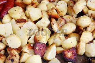 smoked pork sausages and fried potato  in big iron black frying pan
