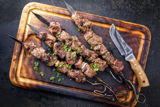 Traditional Russian shashlik on a barbecue skewer as top view on an old burnt cutting board