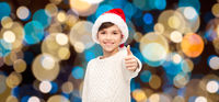 boy in santa hat showing thumbs up at christmas