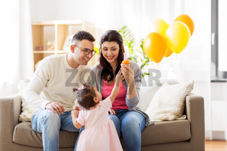 baby girl with parents at home birthday party