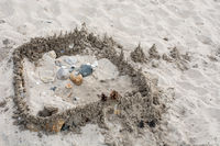Sandschloss am Strand mit Steinen und Muscheln