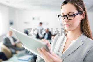 Geschäftsfrau mit Brille bedient Tablet Computer