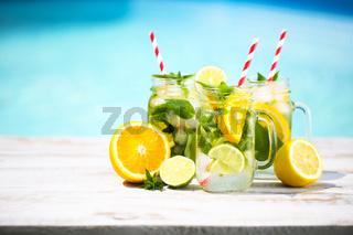 Glasses of citrus lemonade near pool