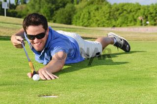 Junger Golfer liegt auf dem Green und puttet