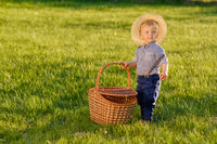 Toddler child outdoors. One year old baby boy wearing straw hat holding picnic basket