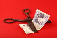 Scissors cut British Pound over red background