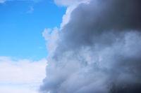 Huge white cumulus clouds against blue sky in spring.
