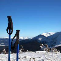 Ski poles in snow and snow-capped mountains at sun winter day