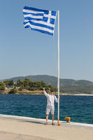 Tourist near Greek flag on the Aegean coast of Sithonia peninsula