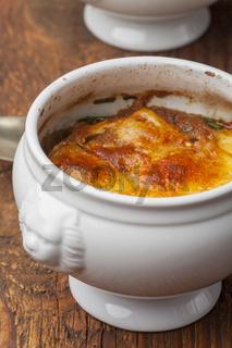 Französische Zwiebelsuppe mit Käse auf Holz