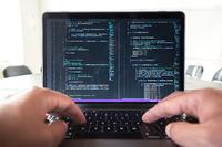 Programmer profession - man writing programming code on laptop computer.