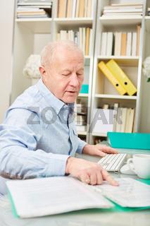 Älterer Geschäftsmann kontrolliert Akten