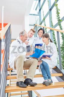 Ärzteteam in einer Besprechung im Treppenhaus