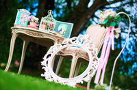 Retro styled chair, table and white carved frame. Pretty things, symbols of Alice in Wonderland