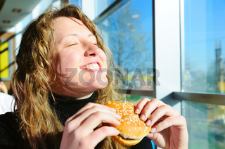 very happy woman is eating cheeseburger