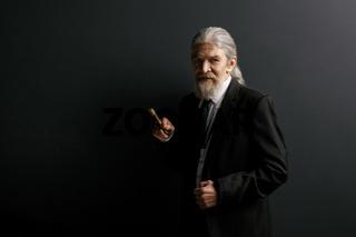 Elrderly stylish man in black jacket holding cigar.