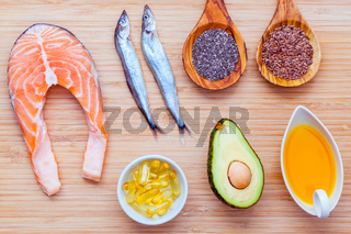 Selection food sources of omega 3 and unsaturated fats. Super food high vitamin e and dietary fiber for healthy food. Olive oil ,flax seed ,chia ,fish oil ,avocado ,shishamo fish and salmon on bamboo cutting board.