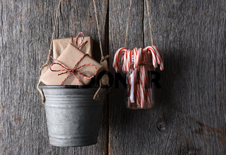 Presents and Candy Canes Hanging against a rustic wood wall