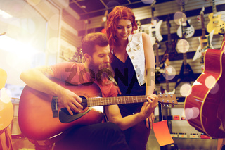 couple of musicians playing guitar at music store