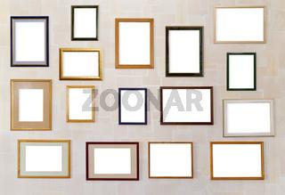 Many various photo frames  hang on a wall.