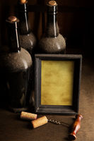 Dusty wine bottles and blank picture frame