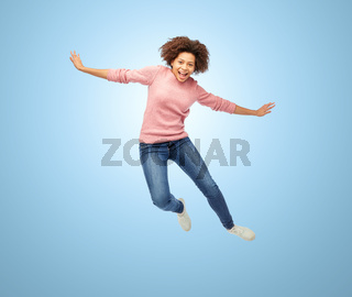 happy african american woman jumping over white