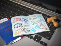 Visa online application concept. Open passport with visa stamps with airline boarding pass tickets and stamper on the computer keyboard.