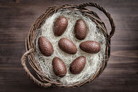 Delicious chocolate Easter eggs and a basket on wooden background