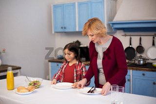 Grandmother and granddaughter lay the table