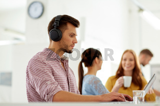 creative man in headphones with laptop at office