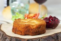 Panierter Camembert mit Salat auf Holz