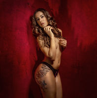 Posing brunette girl in lingerie on red textured background, sensual scene