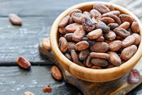 Fragrant cocoa beans in wooden bowl closeup.