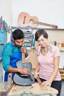 Zwei Lehrlinge bauen eine Gitarre zusammen