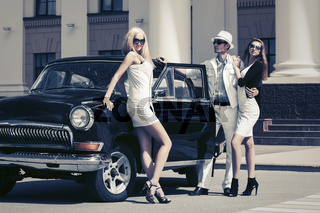 Young fashion people next to vintage car