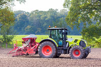 Tractor with agricultural machine on land